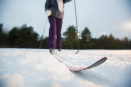One of skis on ski track in snow with human moving forwards along it Stock Photo