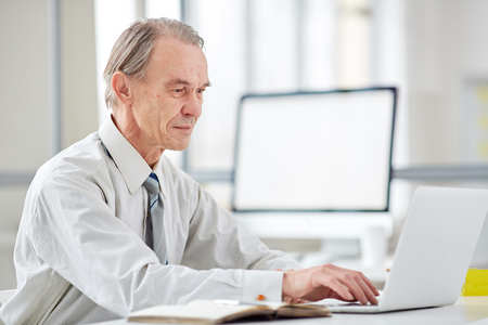 Authentic elderly worker typing on laptop in office with glass walls
