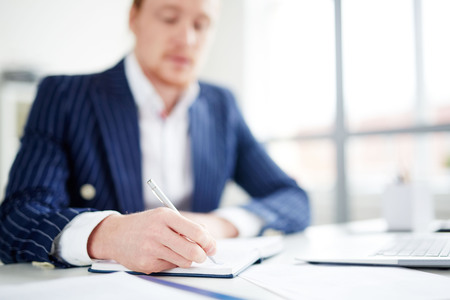 Businessman sitting at table and making notes