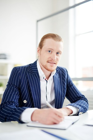 Portrait of redheaded businessman working at office