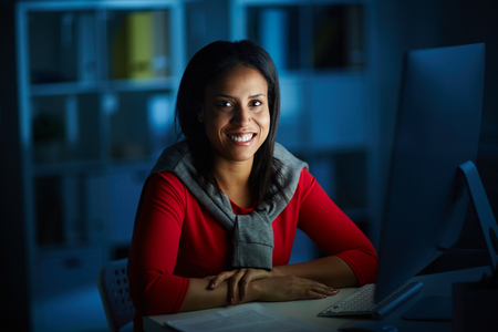 Portrait of a smiling businesswoman sitting at her workplace at dark office