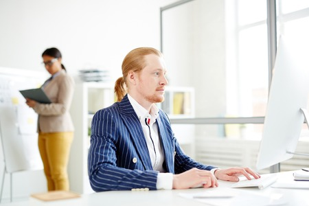 Businessman using computer at the table with woman in the background