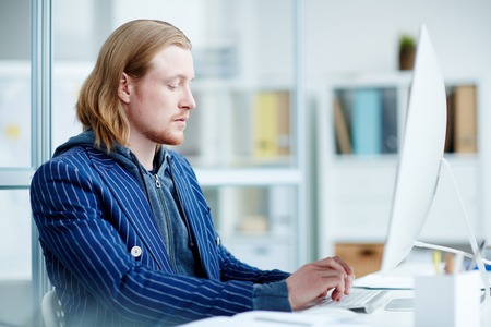 Businessman sitting at office desk, working on desktop computer Stock Photo