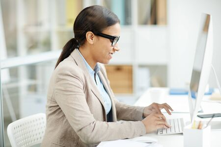 Smiling secretary in eyeglasses typing on computer at office