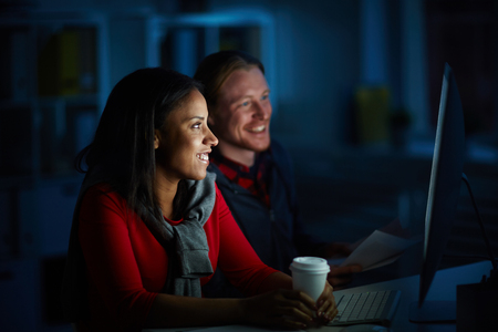 Businessman and businesswoman working on computer till night