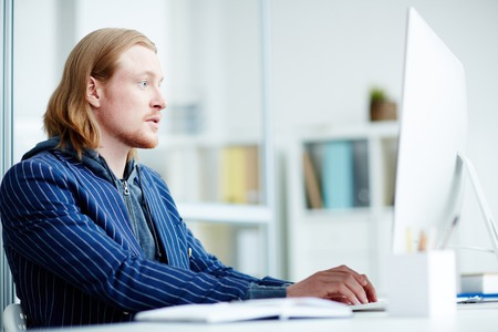 Redheaded serious businessman typing on computer at the table Stock Photo