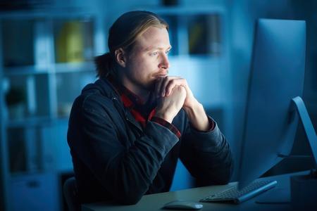 Ernstige man kijkt naar een computerscherm in een donker kantoor