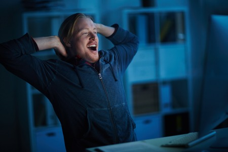 Businessman yawning while working on computer at office Stock Photo