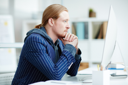 Concentrated businessman thinking about new project. He is using computer