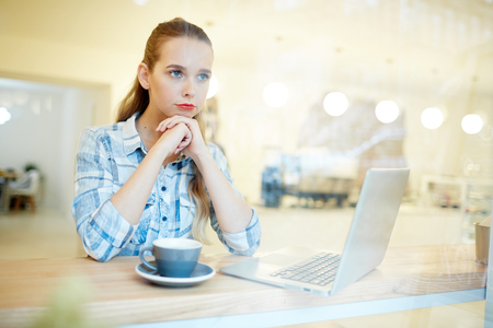 Young woman worried about the new business project. She is sitting in the coffee shop