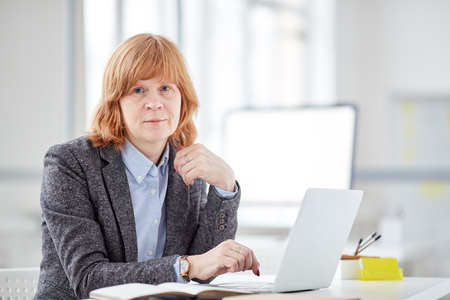 Portrait of mature female office worker with red hair looking at camera while using laptop 写真素材