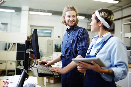 Two operators working on printing machine in team