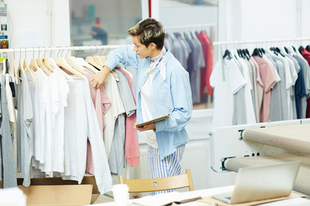 Young woman working with her new collection in workshop