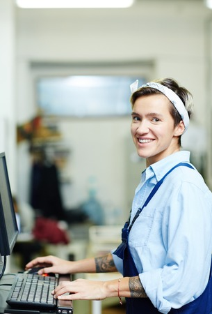 Female operator typing on computer in printing house