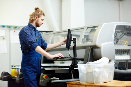 Typographer working with printing machine on factory