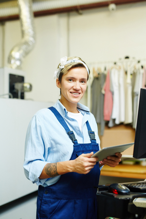 Portrait of woman with touchpad standing in printing house