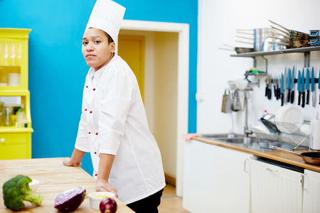 Female chef leaning against table and looking at camera while going to cook