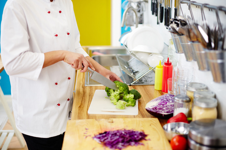 Restaurant chef with knife cutting fresh broccoli on board before cooking stew