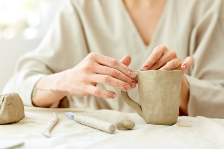Hands of artisan making clay or ceramic mug by workplace with necessary handtools near by Stock Photo