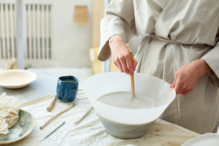 Young creative handcraftswoman mixing clay powder with water in plastic bowl on table Standard-Bild - 98460109