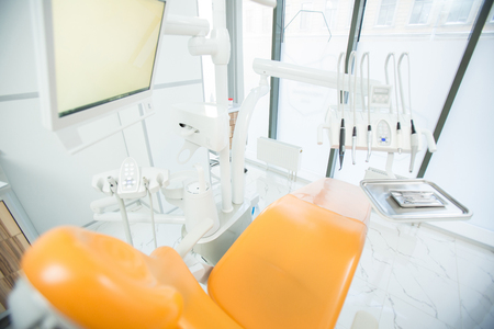 View of leather armchair for patients with monitor above and dentistry equipment in front