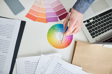 Close-up of male hands of designer working with color samples