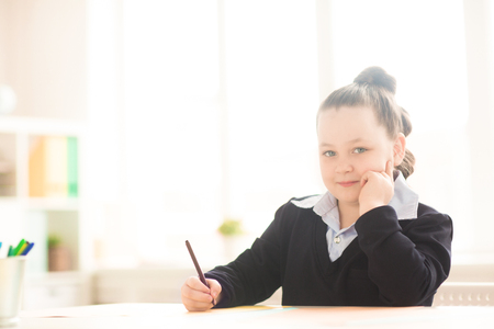 Portrait of lovely schoolgirl sitting at the desk and drawing