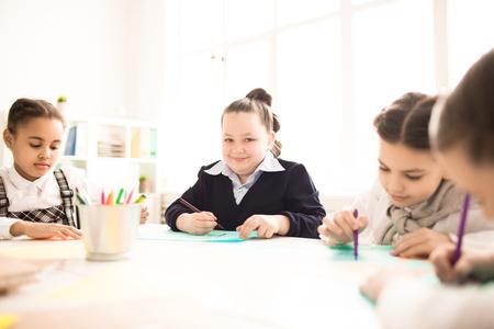 クラスメートと一緒にテーブルで勉強している女子高生。絵を描く