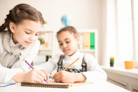 Two schoolgirls drawing together in notepad at classroom