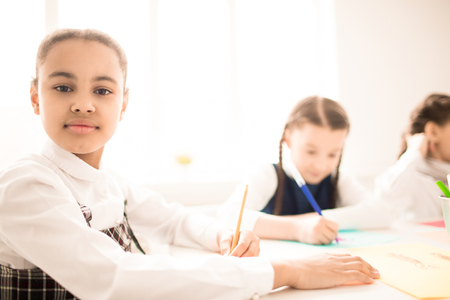 Portrait of African schoolgirl sitting at desk and writing Imagens - 98987058
