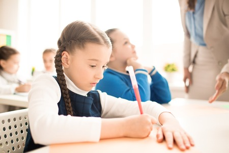 Serious schoolgirl doing exercise at the table at classroom