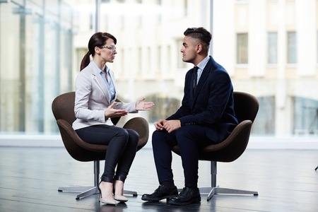 Profile view of confident dark-haired entrepreneur sitting opposite her business partner and discussing details of mutually beneficial cooperation, interior of boardroom on background Stock Photo