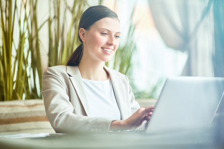 Young attractive Caucasian woman talking to business partner on laptop and smiling cheerfully while having lunch break in cafe Foto de archivo