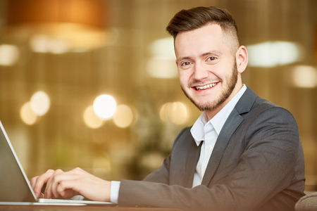 Portrait of young handsome Caucasian man in business suit sitting at laptop and smiling at camera cheerfully on blurred background