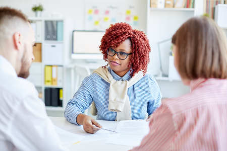 Stylish African American female manager with red curly hair having business meeting with colleagues in office