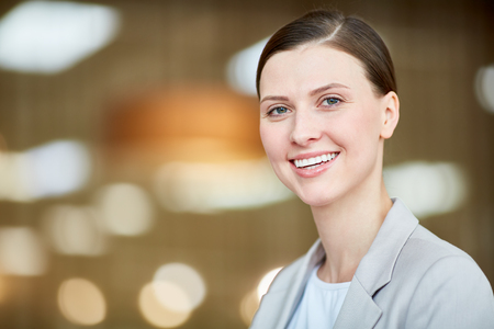 Portrait of young beautiful caucasian female worker smiling at camera cheerfully on blurred background Фото со стока