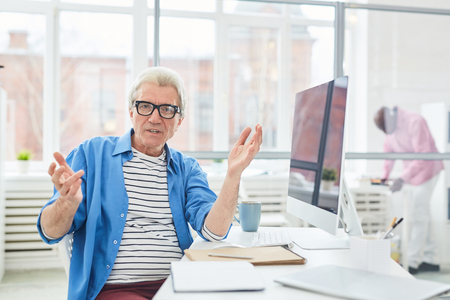 Gray-haired businessman gesturing while sitting at his workplace