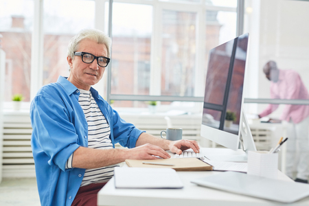 Casual senior businessman sitting at his desk and working. He is wearing eyeglasses and typing on computer