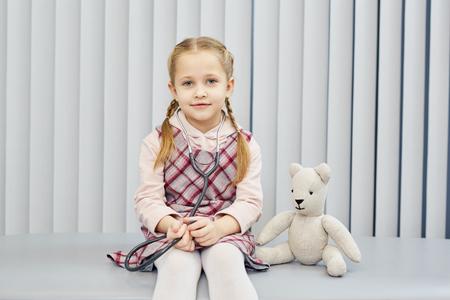 Portrait of little girl sitting at doctor's office Foto de archivo