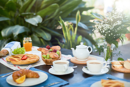 Fresh croissants, sweet homemade pie for tea and fresh fruits on served table in orangery or home-garden Stock Photo
