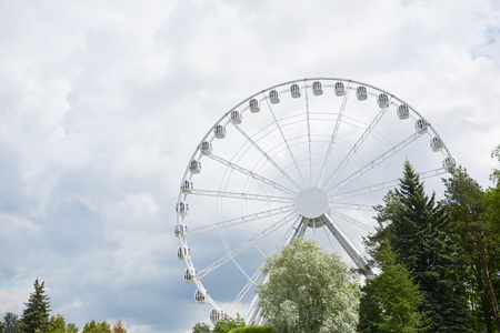 Ferris wheel in contemporary amusement park among green and blooming trees and grey cloudy sky