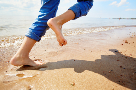 Barefoot child running on sandy beach along coastline while enjoying summer vacation or weekend