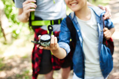 Young boy scout his companion walking after compass arrow while looking for the camp in the forest
