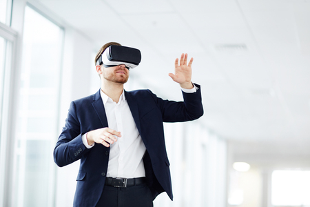 Young businessman using virtual reality technology at work