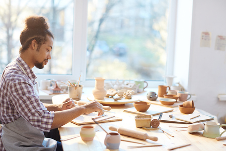 Side view of mixed race male potter making beautiful clay souvenirs while sitting at table in workshop Stock Photo
