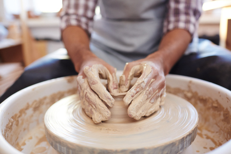 Unrecognizable male potter molding clay vase spinning on pottery wheel in workshop, close-up view Stock fotó