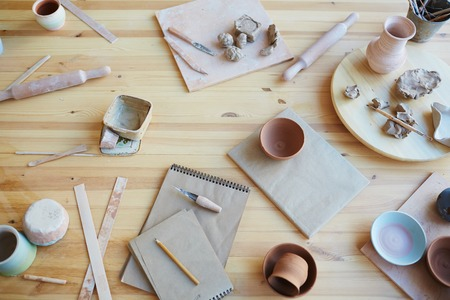 High angle view of pottery tools and clay handicrafts lying on wooden table in workshop