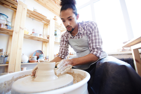 Low angle view of young concentrated mixed race man making clay jar on pottery wheel in workshop