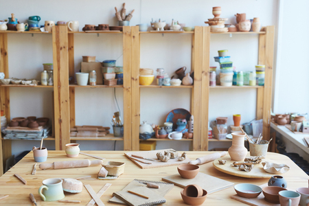 Messy workshop with handmade clay vases, pots and jars made by professional potter