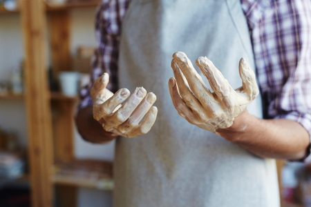 Unrecognizable male ceramist standing in workshop with hands in clay after making earthenware on pottery wheel Stock fotó